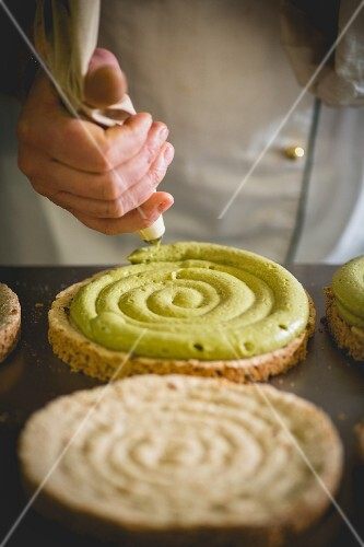 A confectioner piping pistachio cream on a sponge base