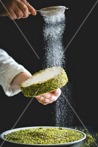 A confectioner dusting a small pistachio cake with icing sugar