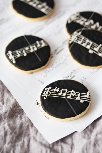 Round cookies with black icing on a piece of sheet music