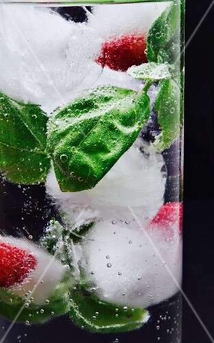 Ice cubes with raspberries and basil in a glass of water