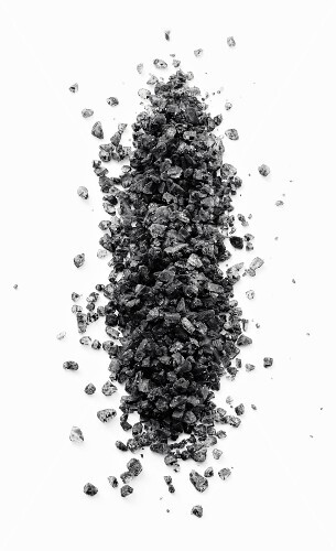 A pile of black vulcan salt on a black surface