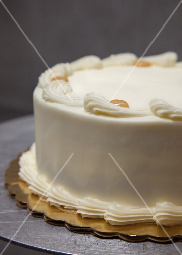 A whole layer cake with buttercream and caramel dots