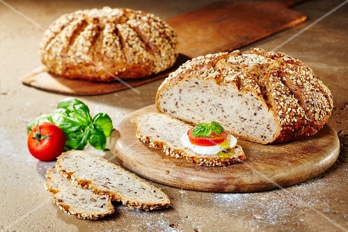 Two loaves of multigrain quark bread with tomatoes, mozzarella, basil and olive oil