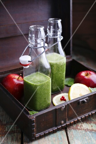 Spinach and banana smoothies in bottles in a wooden crate