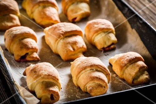 Freshly baked croissants on a baking tray