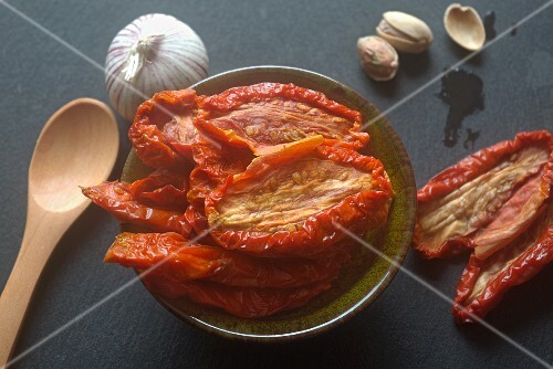 A bowl of dried tomatoes next to garlic and pistachio nuts