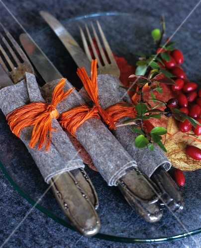 Silver cutlery wrapped in felt and raffia on glass plate