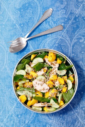 Spinach salad with baked chicken breast, cucumber, mango and sunflower seeds