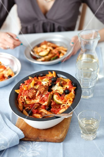 Penne pasta with meatballs, vegetables and olives