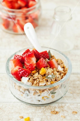 Homemade mango and coconut muesli with vanilla and fresh strawberries
