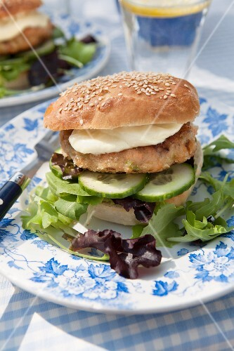 A fish burger with cucumber, lettuce and mayonnaise