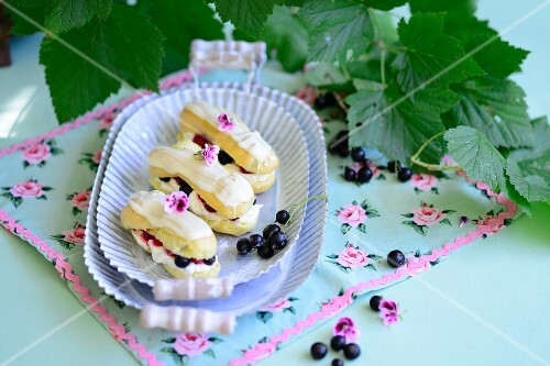 Eclairs with cream and blackcurrants