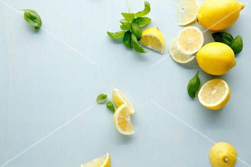 Lemons and basil on a white surface