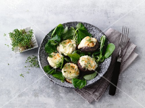 Mushrooms filled with cheese on a bed of lamb's lettuce