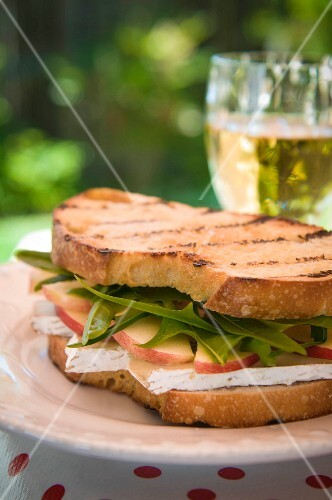 A sandwich with Brie, apples and dandelion leaves
