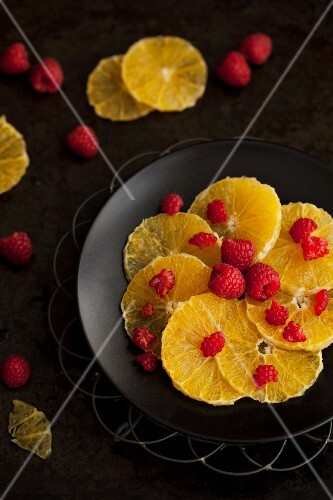 Orange slices and raspberries on a plate