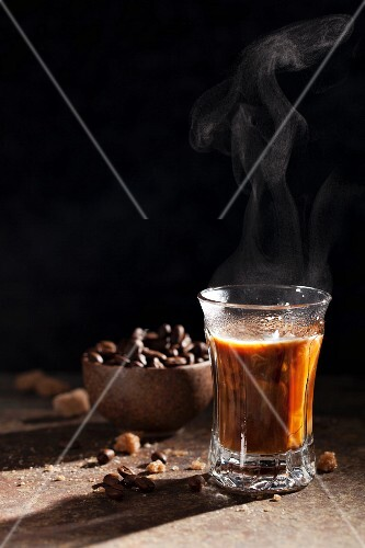 A steaming glass of coffee with coffee beans and sugar lumps in the background