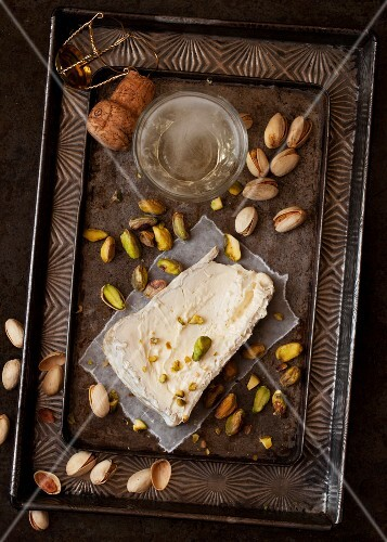 A slice of Delice de Bourgogne soft cheese served with pistachio nuts and champagne