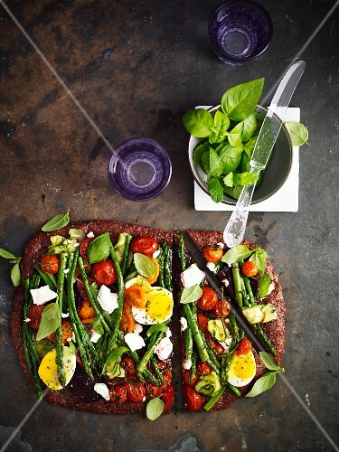 Wholemeal pizza topped with vegetables, feta cheese and egg