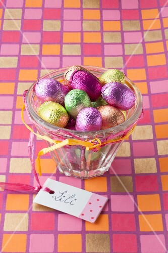 Chocolate Easter eggs in coloured foil in a glass bowl with a gift tag