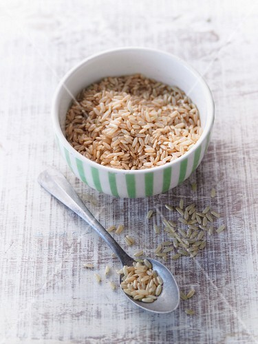 Natural rice in a porcelain bowl and on a spoon