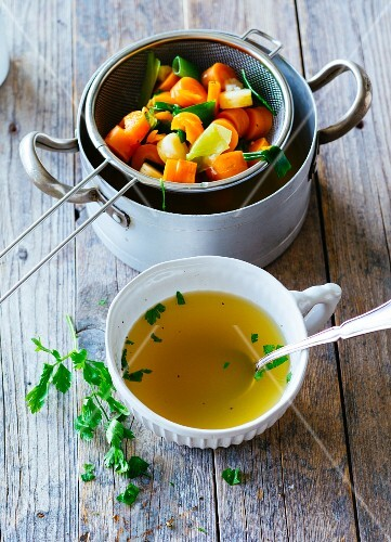 Carrot and vegetable stock in a soup cup