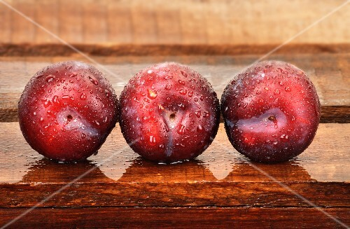 Three plums with droplets of water on wooden crate