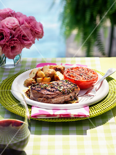 Bacon-wrapped fillet steak with grilled tomatoes and fried potatoes