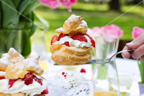 A profiterole filled with strawberries and cream on a cake slice