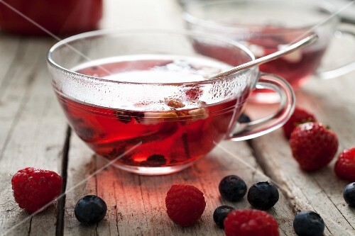 A cup of tea with berries