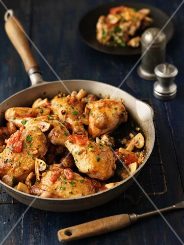 Fried chicken with tomatoes and mushrooms in a pan