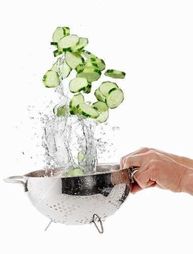 Cucumber slices being washed in a sieve
