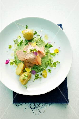 Salmon fillet with herb sauce, edible flowers and potatoes