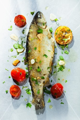 Fried trout with herbs, garlic, tomatoes and lemons