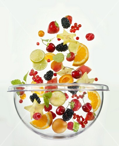 Various fruits falling into glass bowl