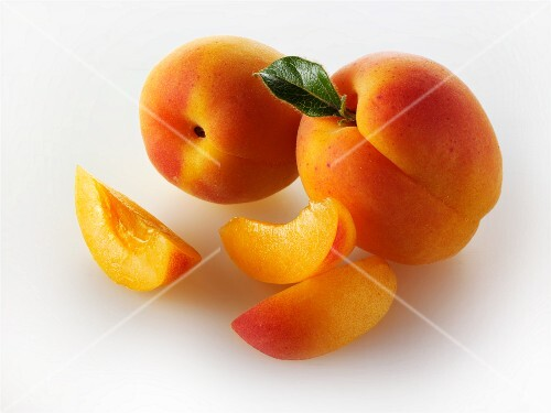Two whole apricots and apricot slices