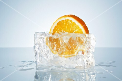 Half an orange in a block of ice
