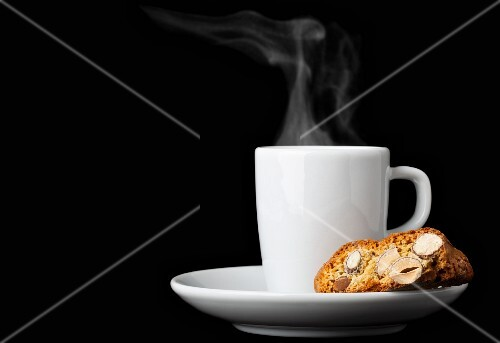 Biscotti (Italian almond biscuits) and a cup of espresso against a black background