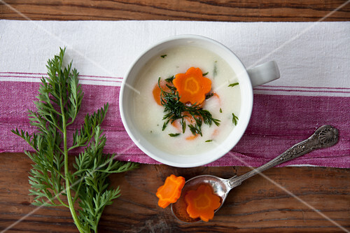 Cream of potato soup garnished with carrots and carrot leaves
