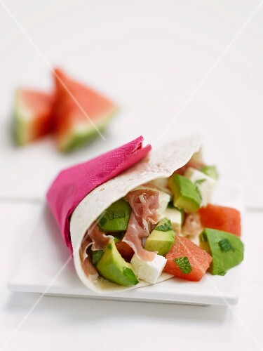 A wrap filled with avocado, Prosciutto ham and watermelon