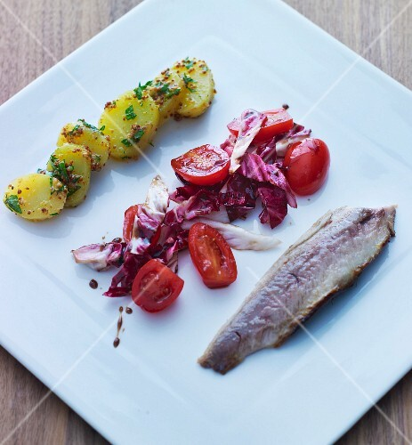 A herring fillet, tomato salad and potatoes (Scandinavia)