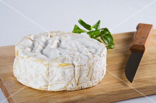 Camembert and a knife on a chopping board
