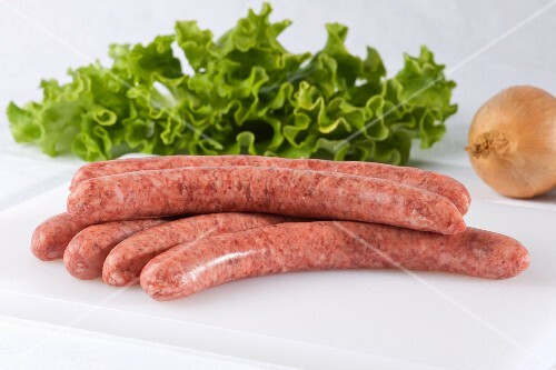 Raw pork sausages, mixed leaf salad and an onion