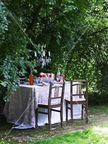 Dark wood chairs at table with tablecloth in garden