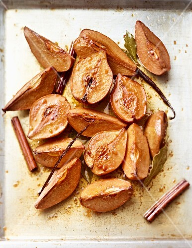 Quinces on a baking tray with vanilla, cinnamon and bay leaves
