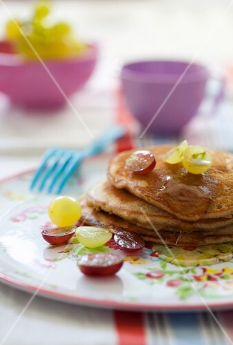 Pancakes with grapes and maple syrup