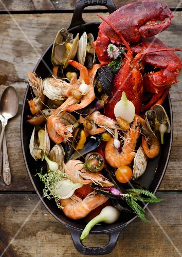 Seafood Aquatto Stew in a Cast Iron Pot on Wooden Table