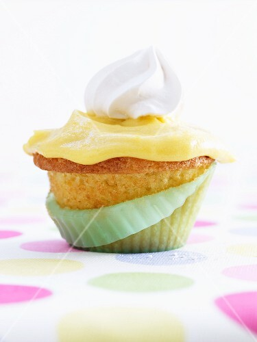 A lemon and rosemary cupcake topped with a dollop of cream