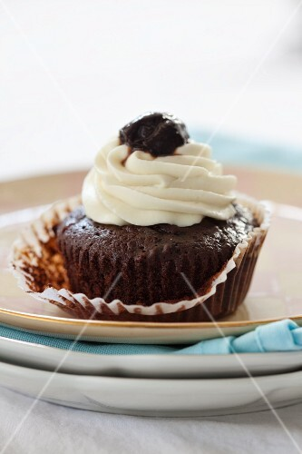 A chocolate cupcake topped with cream