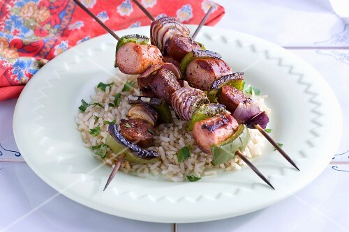 Sausage kebabs with onions and peppers on a bed of rice